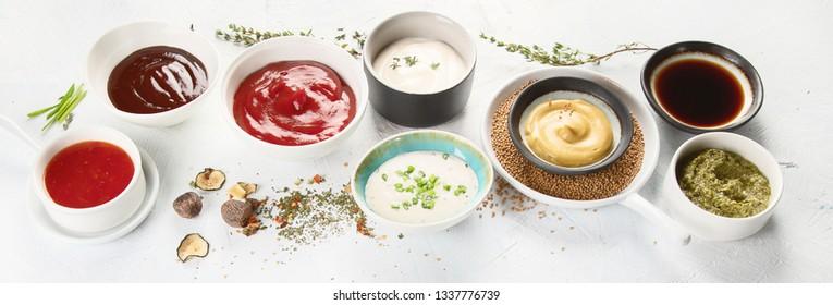Bowls of various sauces - ketchup, mayonnaise, barbecue, soy, mustard, pesto, garlic, sweet chilli. Panorama,banner
