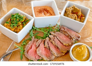 Bowls with various starters and sliced roast beef.