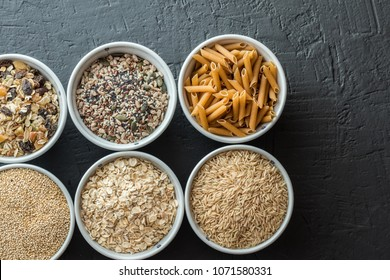 Bowls with whole grain carbohydrates, oats, brown rice, seeds, quinoa and whole grain pasta. Healthy food concept