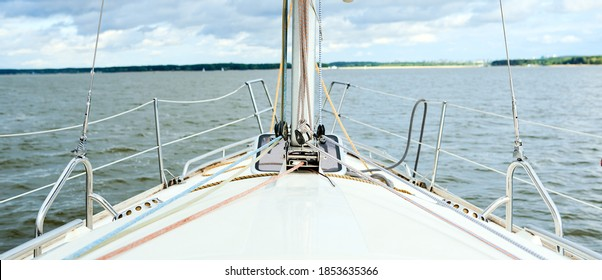 Bows of a yacht sailing offshore in summer in a first person point of view on a calm ocean