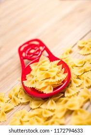 Bowtie pasta on an red spoon holder. Pasta spread out around spoon holder. All setting on a wooden table