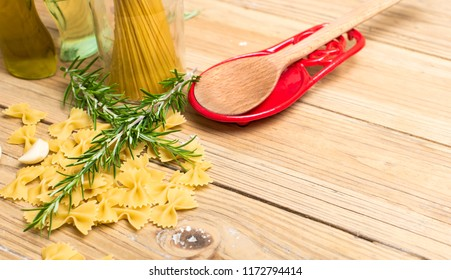Bowtie pasta with wooden spoon setting on an red spoon holder. Rosemary sits on top of pasta. Setting on wooden table.