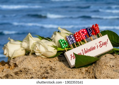"box of candles with the inscription ""Happy Valentine's Day"" against a flowers and a sea background"