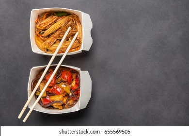 box of Chinese food and chopsticks on dark background