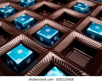 Box with chocolate candies in a blue wrap.