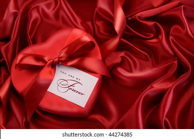 Box of chocolate with red ribbon on satin
