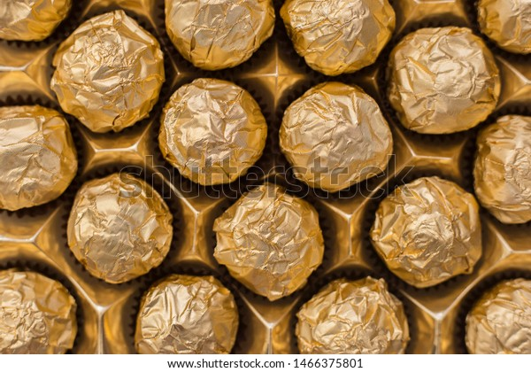 Box of chocolates in golden foil. Close-up chocolate candies in gold foil. Chocolate candy background. Gold foil background