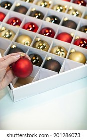 Box of Christmas ornaments in assorted colors with hand. Shot with copy space.