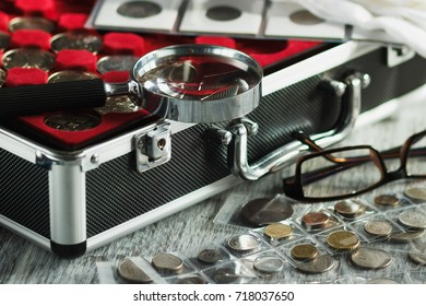 Box with collector's coins, magnifying glass and glasses, soft focus background