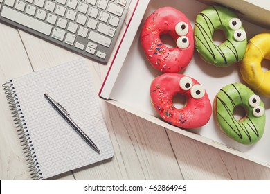 Box of colorful glazed donuts with funny eyes on the office desk near computer keyboard and notepad with pen. White rustic wooden table with business lunch snack dessert top view
