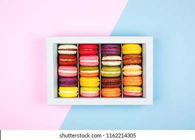 Box of colorful macarons on trendy blue and pink background . Flat lay style.
