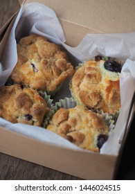 box of crumble blueberry muffins on wooden table