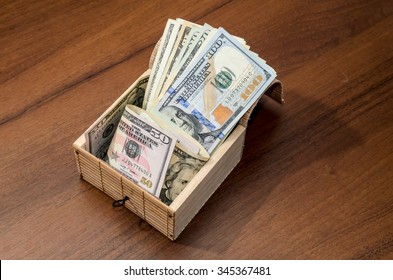 Box with dollar bills on wooden background