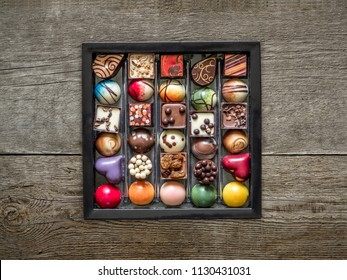 Box of fancy chocolate fondants on wooden surface