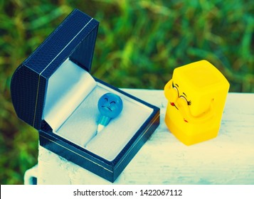 A box with a figure and a figure with closed eyes. The concept of mourning the deceased, funeral, mourning, at the tomb. people, crying person with coffin at funeral.