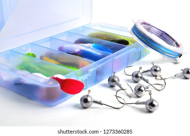 Box for fishing accessories with silicone baits inside, Jig hooks, braided reel on a white background close-up