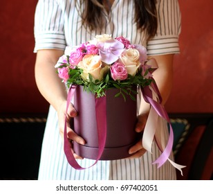 box of flowers with ribbon in girl hands. concept of lady with lilac orchid bunch in floristry shop like banner for little luxury shop