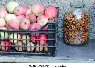 Box of fresh colorful apples and a jar of dried apples on the grey bench, preparing apples for winter