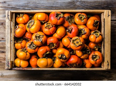 Box of fresh fruit persimmon kaki on wooden background. Top view