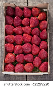 Box of fresh strawberries on wooden background