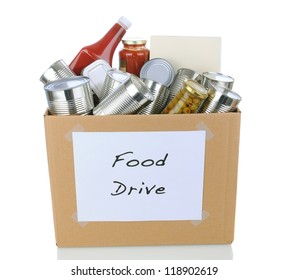 A box full of canned and packaged foodstuff for a charity food donation drive. Isolated on white with reflection. Cans have no labels and the box has a hand made sign.