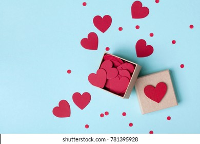 Box full of red hearts and confetti on blue table top view. Valentines day background. Flat lay style.