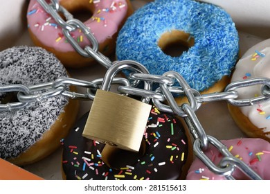 box full of tempting delicious donuts wrapped in metal chain and lock in sugar and sweet addiction and diet body and dental care concept