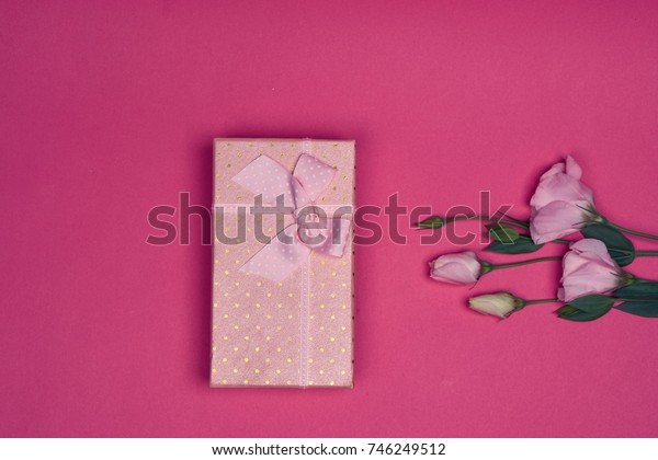 box with a gift, flowers fresh on a pink background top view, holiday