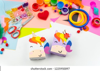 A box with a gift inside in the form of a rainbow unicorn. Children's paper craft school kindergarten. Party with a surprise.