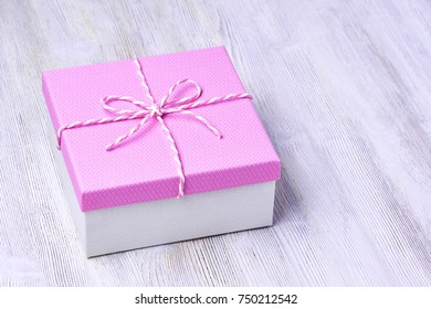 Box of gifts on white wooden background tied with string