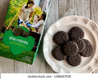 Box of Girl Scout Thin Mints with a few on a white plate on a wooden surface