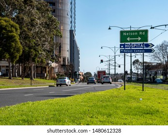 Box Hill, Victoria / Australia - August 2018: Busy road in the suburb of Box Hill, Melbourne. A truck and some cars can be seen in the road, modern building, traffic lights, road signs and trees.