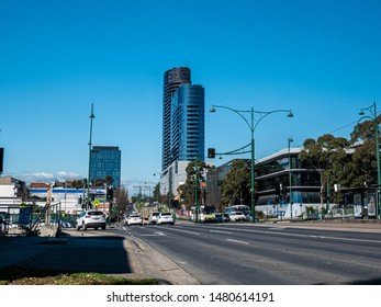 Box Hill, Victoria / Australia - August 2018: White horse road in the suburb of Box Hill, Melbourne. Traffic, tram, buses, modern buildings, foliage, blue sky.