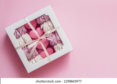 box with marshmallows and macaroons on pink background