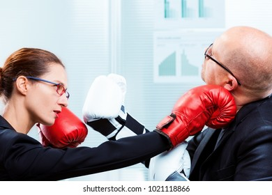 box match between a businesswoman and a business man - concept of man VS woman on the job