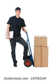 Box moving. Cheerful young deliveryman leaning on the cart with boxes on it while isolated on white