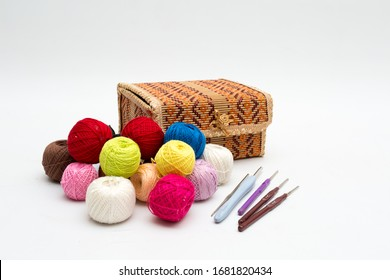 A box for needlework, colorful reels of thread and a set of hooks for home knitting. Still life on a white background