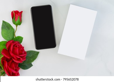 Box of new unboxed Smartphone iPhone next to red roses on marble background, conceptual for giving gift to lover on Valentine's day