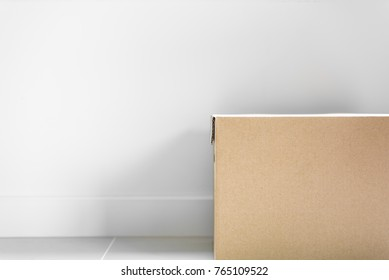 Box package parcel for post delivery on floor with grey wall background. Object and Shape concept. Mail and Post service theme