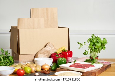 Box with packed meat vegetables on kitchen background. Food delivery services during coronavirus pandemic and social distancing. Shopping online. Dinner delivery service.