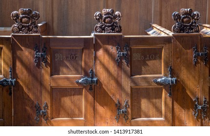 Box pews in a church illuminated by sun. Natural wood texture on hinged doors.
