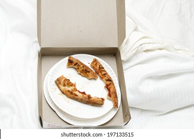 A box with pieces of pizza crust in it.