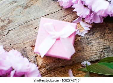 Box. Pink box. Ring inside. Christmas persent. Wooden table. Green leafs. Frame of white and pink flower on the white wooden table