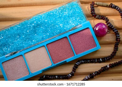 Box with powder and sea salt, beads. Wood background. Colors of Thatch, Silk, Rose Taupe, Mauve Taupe, Maya Blue. Concept of female cosmetics, care, relaxation in the summer.