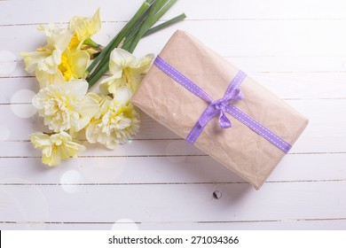 Box with present and spring flowers narcissus  in ray of light on white painted wooden planks. Selective focus.