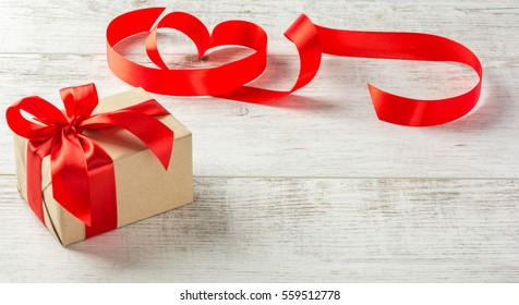 Box with a present to the Valentine's Day  and red tape on a white wooden table