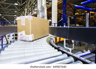 Box with the product moves along the conveyor belt in a modern warehouse