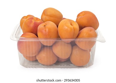 Box or punnet of fresh ripe organic apricots isolated on white background