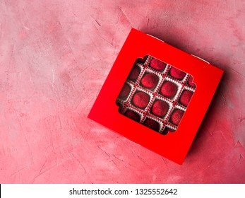 A box of red chocolate truffles coated with sublimated raspberries on a pink concrete background. Delicious gift for any holiday. Copy space.