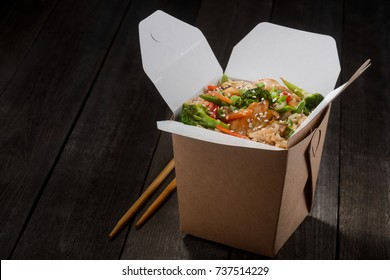 Box of rice and chopsticks on wooden table. Rice fried and stirred with chicken meat, asparagus, spring onion, mushrooms, carrot, broccoli, sesame. Chinese food concept.